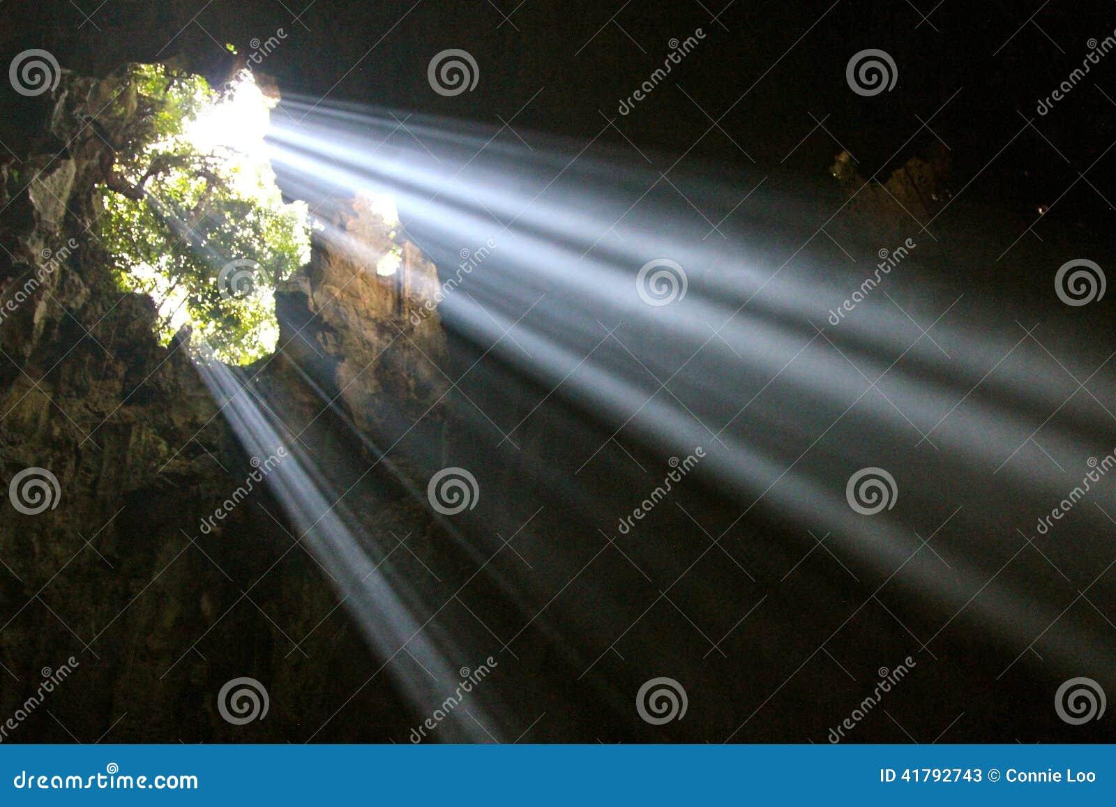 A luz solar perfura as nuvens para criar a iluminação temperamental em um cais da pesca no crepúsculo