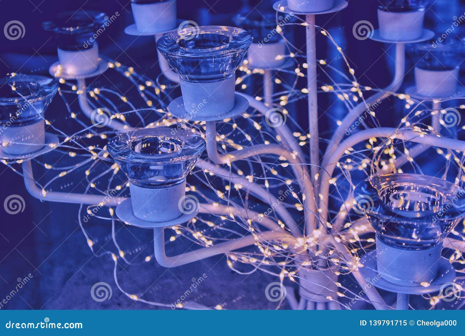 Luzes em torno de um castiçal de vidro luxuoso, uma noite festiva da festão, fundo azul, luzes mornas de incandescência