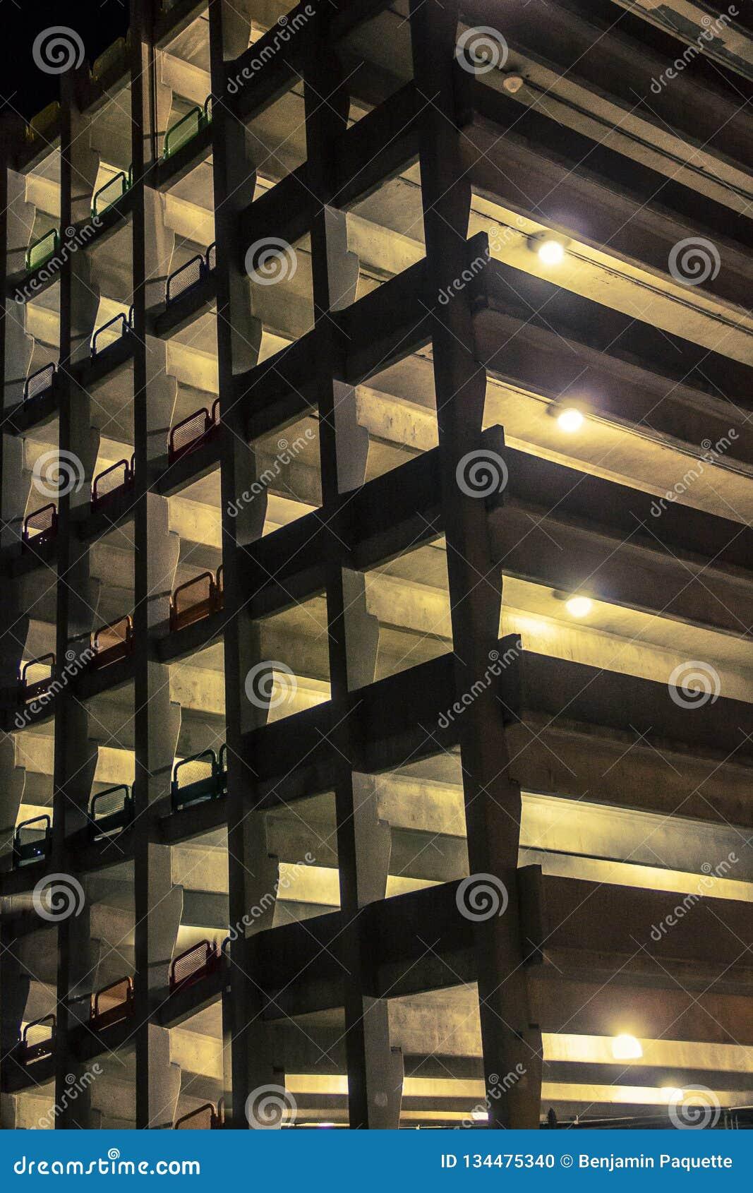 Luzes que incandescem de uma garagem de estacionamento na noite