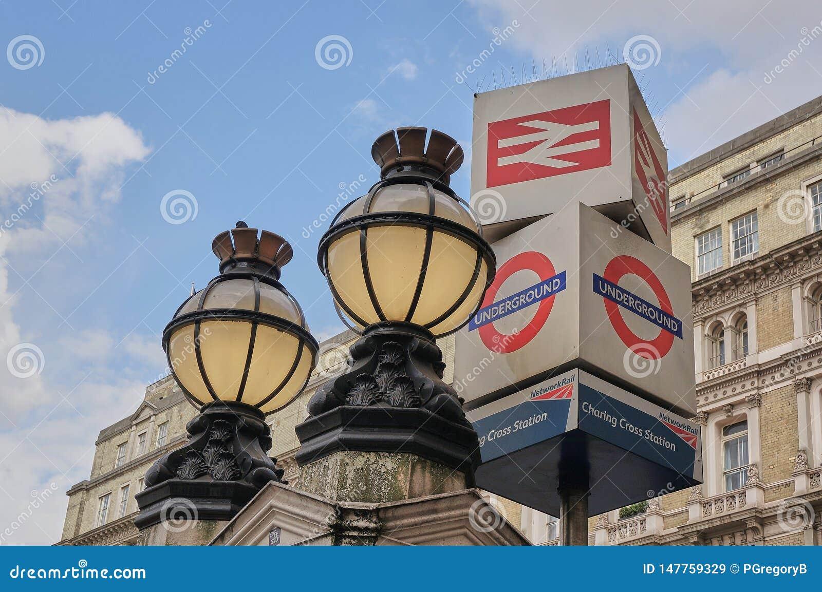 Luzes vitorianos do globo e sinal subterrâneo fora do estação de caminhos de ferro Londres de Charing Cross