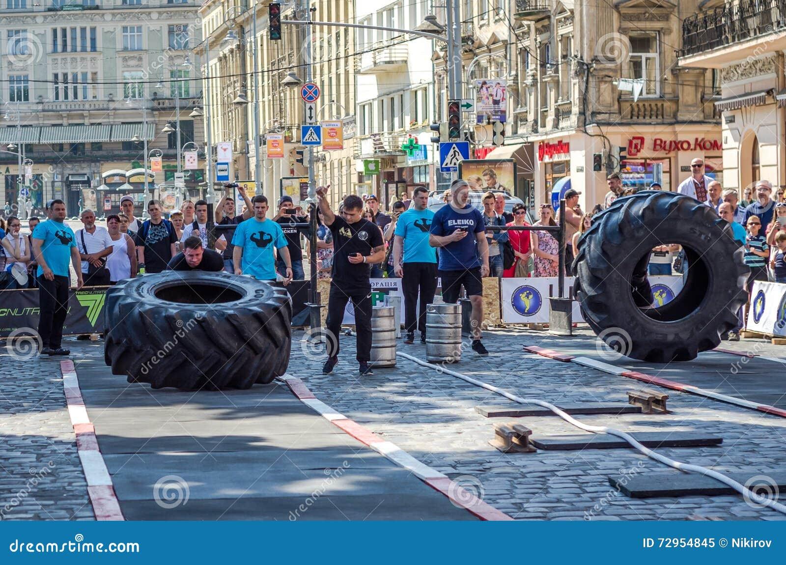 LVIV UKRAINA - JUNI 2016: En stark man i hjulet för lönelyfter för sportformkroppsbyggare det tunga på gatan