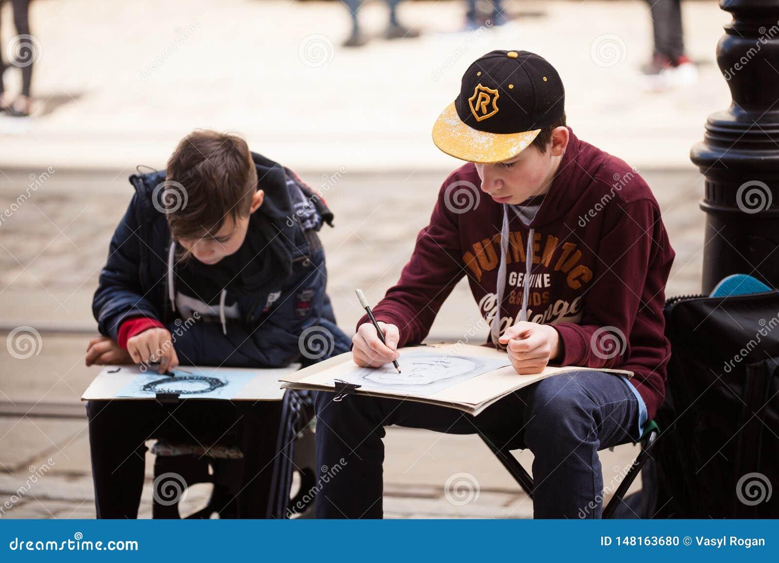 LVIV UKRAINA, Maj 17 -, 2019: Dwa ch?opiec tworz? outdoors nakre?lenia Ucznie maluj? miastowego krajobraz stary Europejski miasto