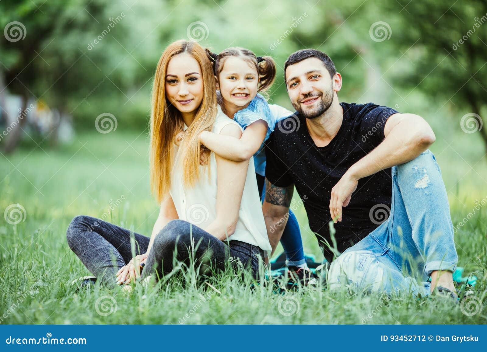 Lycka och harmoni i familjeliv lycklig begreppsfamilj Barnet fostrar och avlar med deras dotter i parkera lycklig familj
