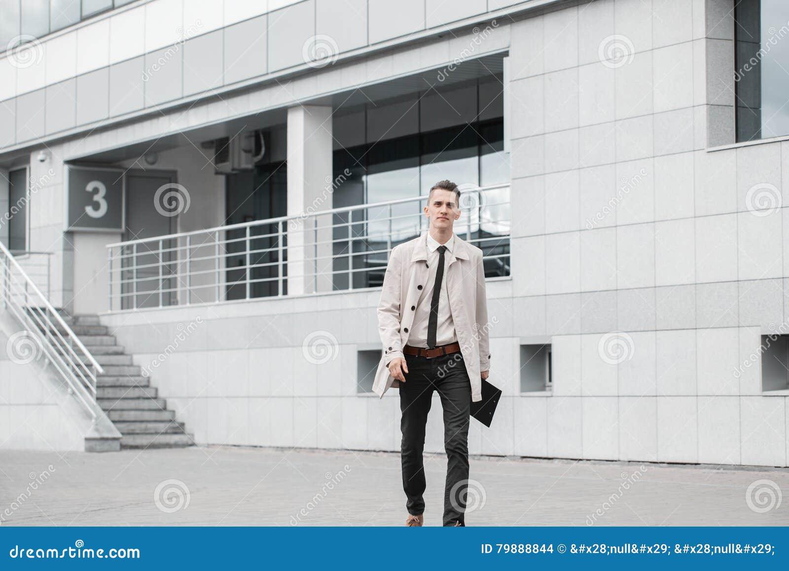 Lyckad affärsman som går ner gatan och ler i dag