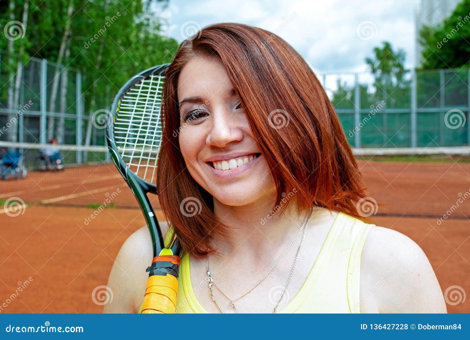 Lyckad idrottskvinna med racket på tennisbanan Sund livsstil