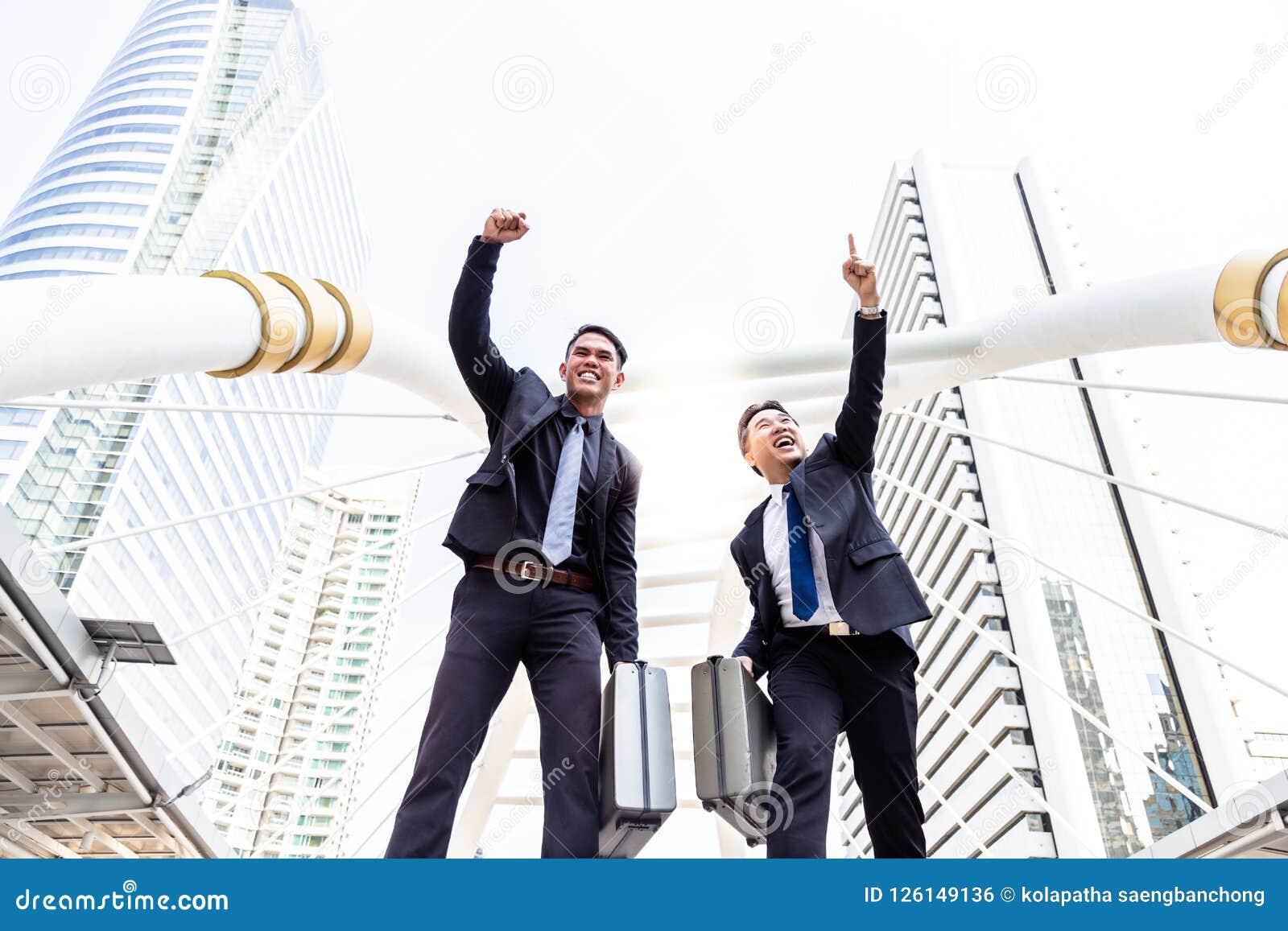 Lyckade affärsmän för stående Den stiliga affärsmannen lyfter