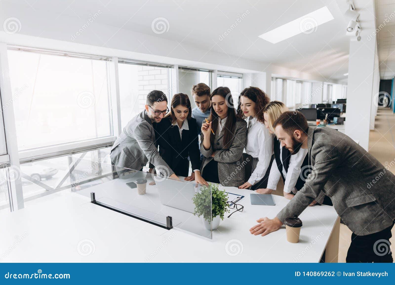 Lyckat lag Grupp av ungt affärsfolk som tillsammans arbetar och meddelar i idérikt kontor