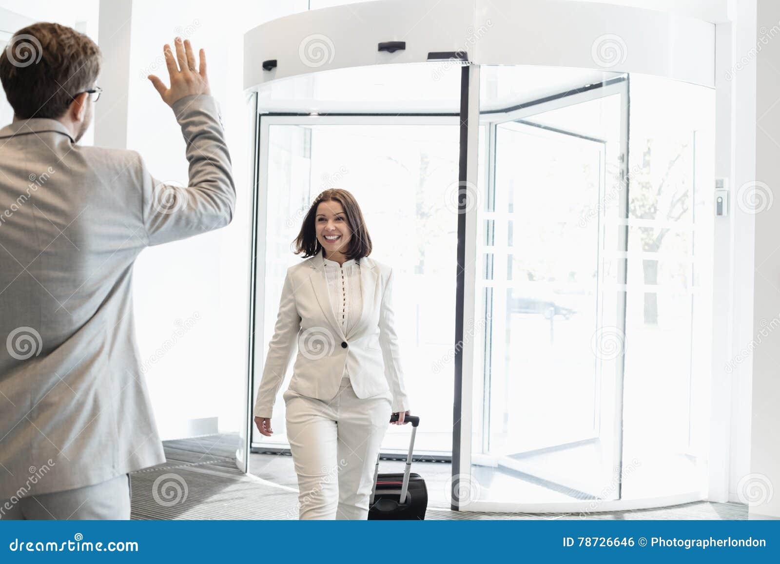 Lycklig affärskvinna med bagage som går in mot den manliga kollegan i konventcentrum
