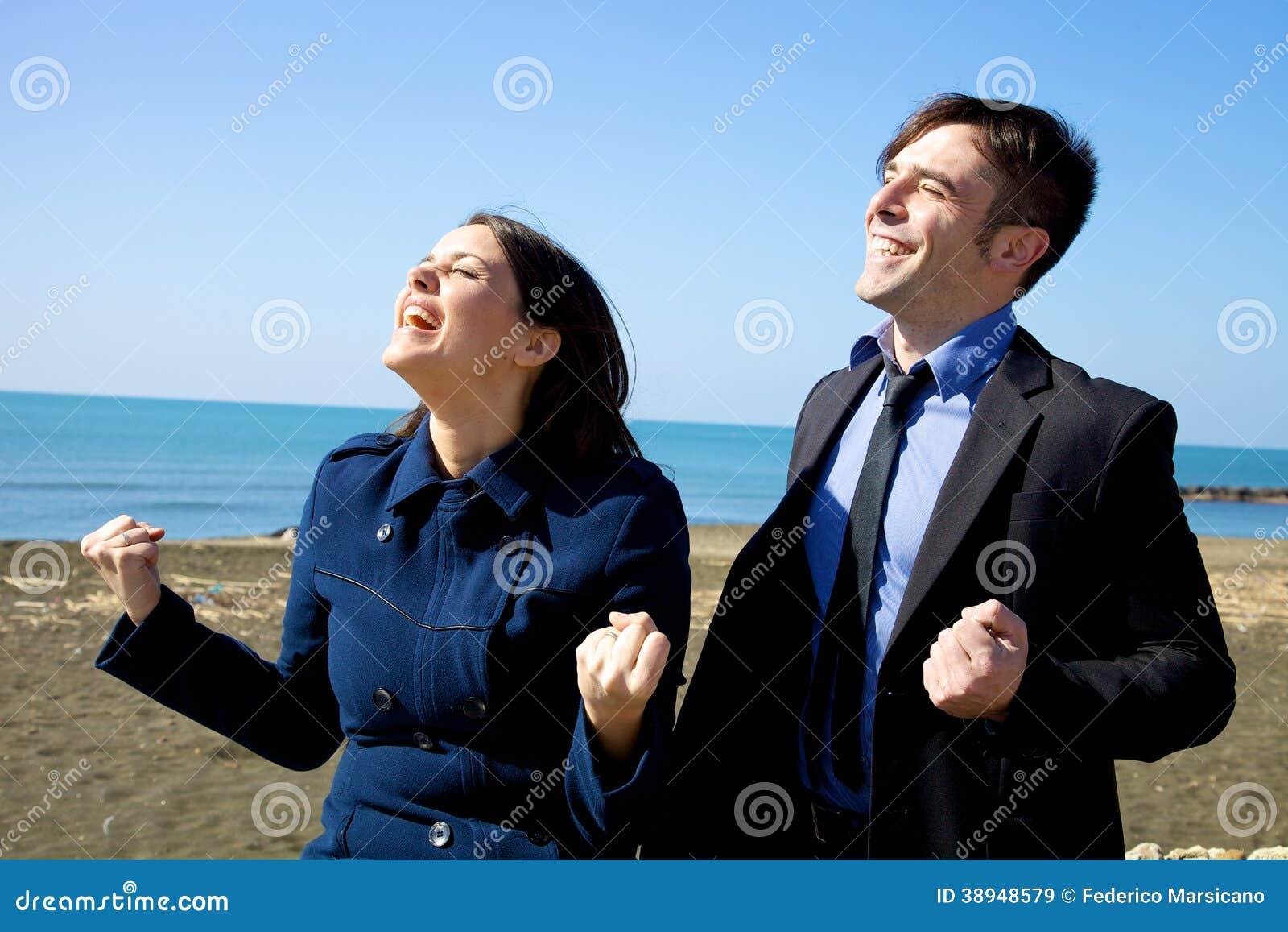 Lycklig affärsman och kvinna som firar det segrade avtalet
