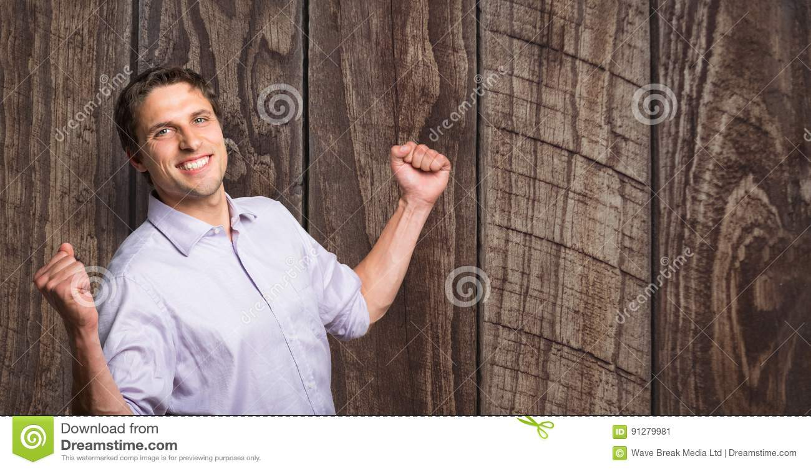 Lycklig affärsman som firar framgång mot träväggen