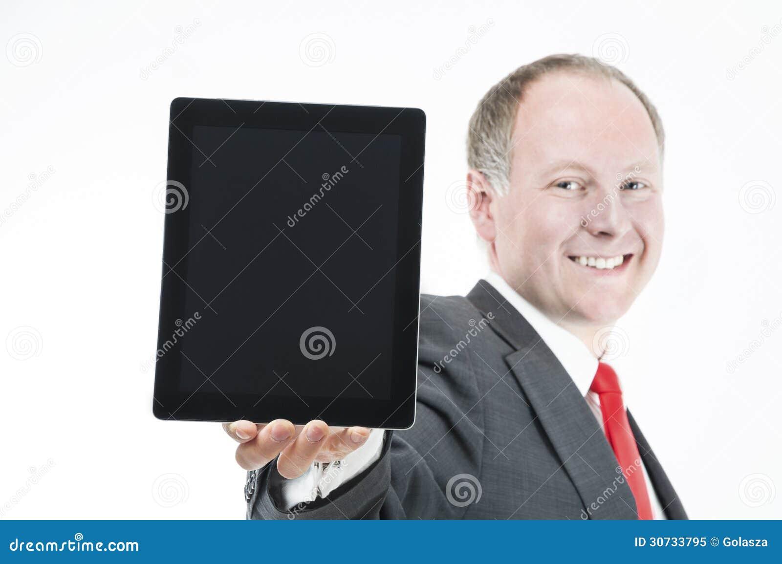 Lycklig affärsman som framlägger (sth på) den digitala minnestavlan