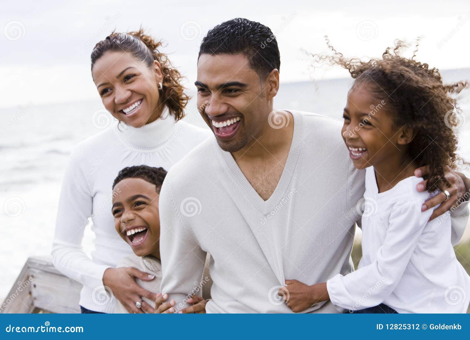 Lycklig afrikansk amerikanstrandfamilj fyra