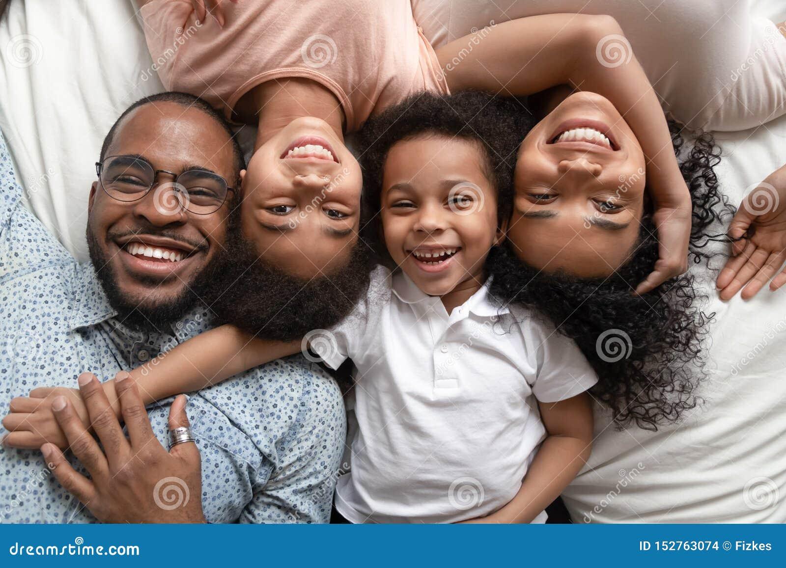 Lycklig afrikansk familj som ligger på sängkeln, stående, bästa sikt