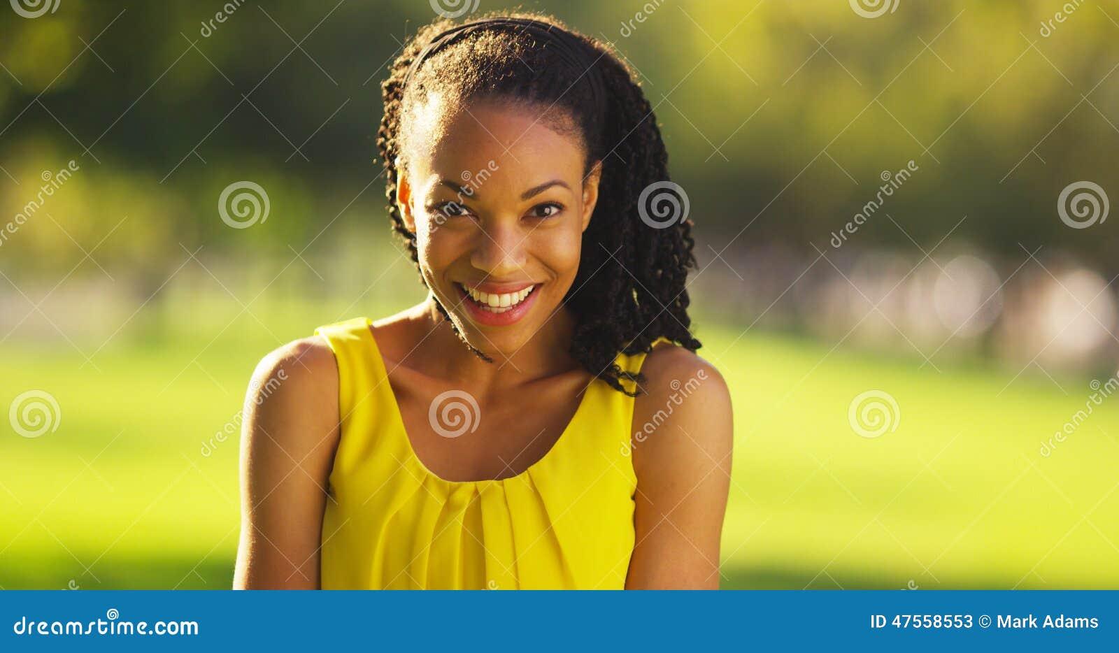Lycklig afrikansk kvinna som ler i en parkera
