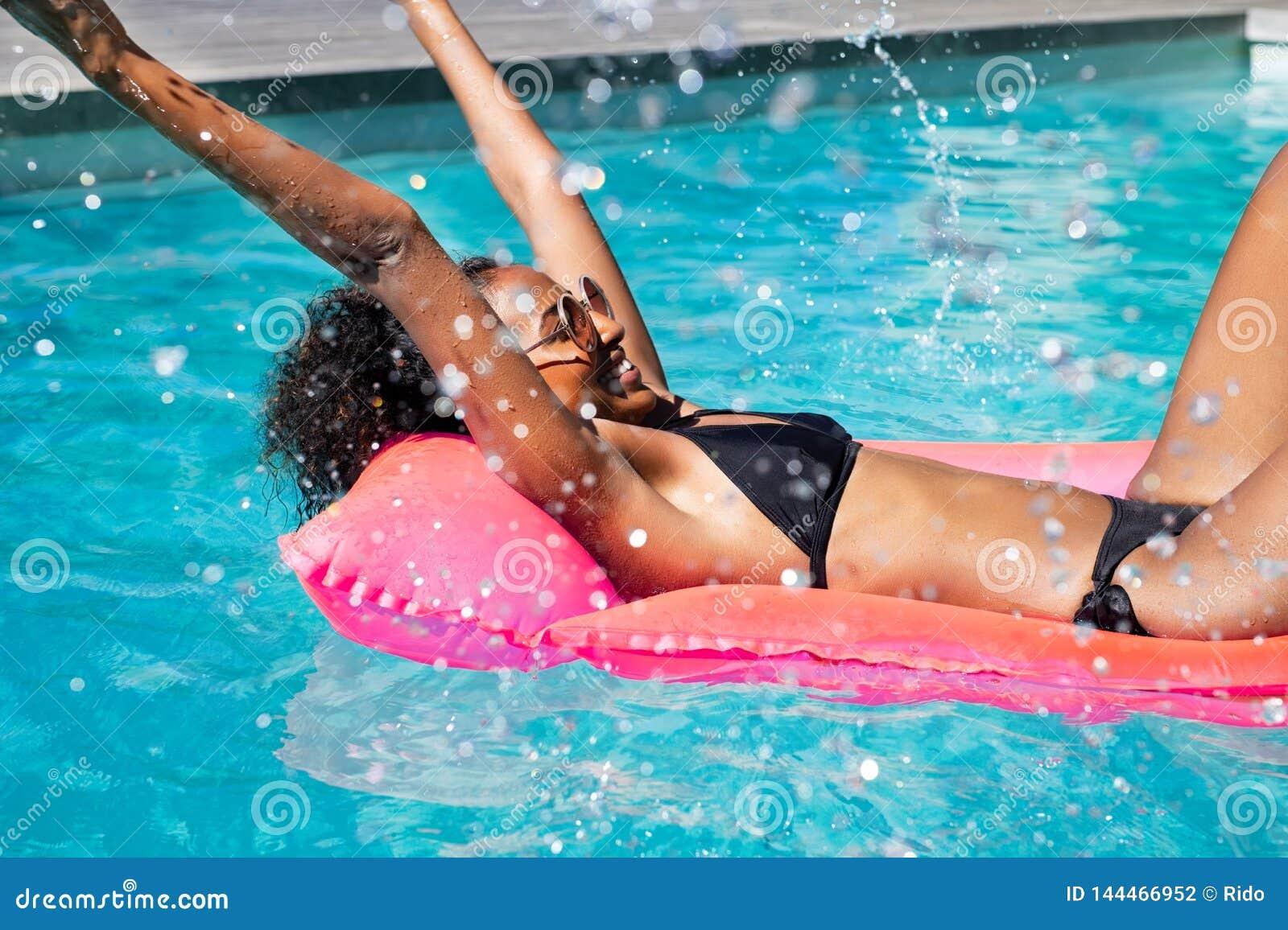 Lycklig afrikansk kvinna som plaskar vatten i pöl