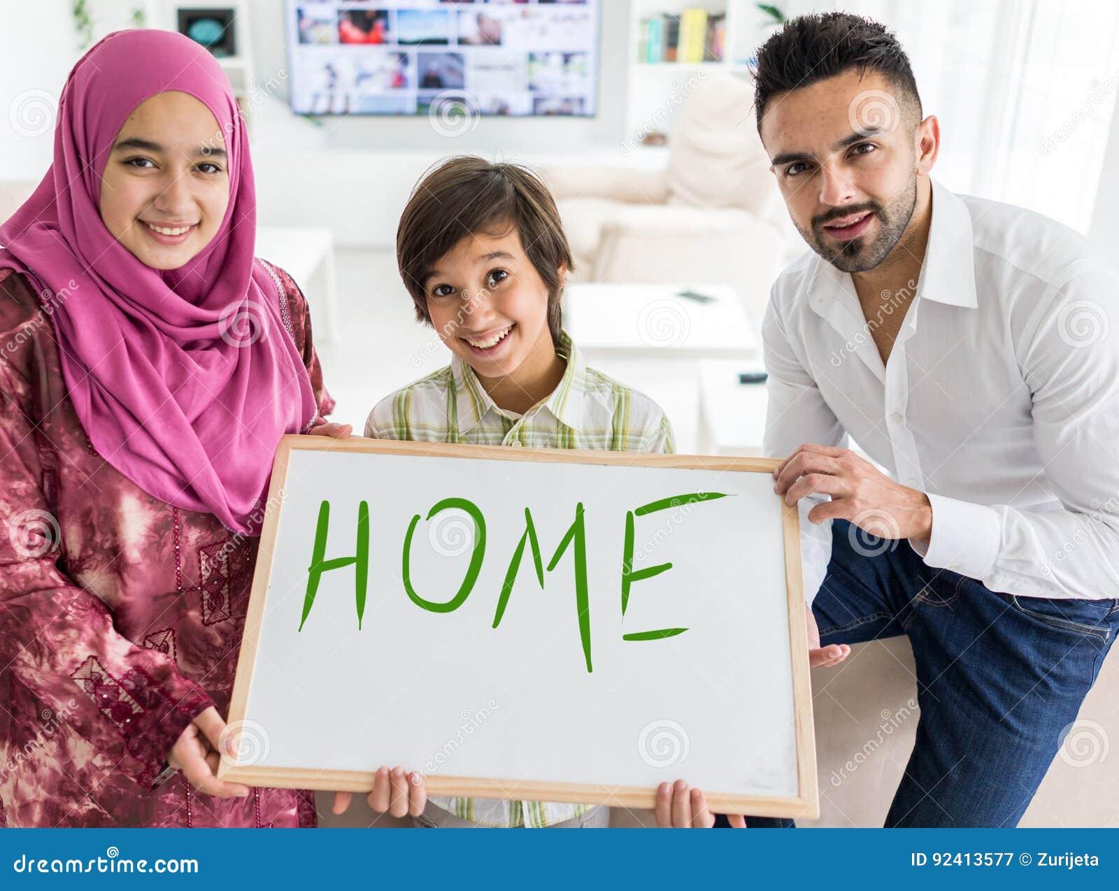 Lycklig arabisk muslimsk familj på det moderna hemmet
