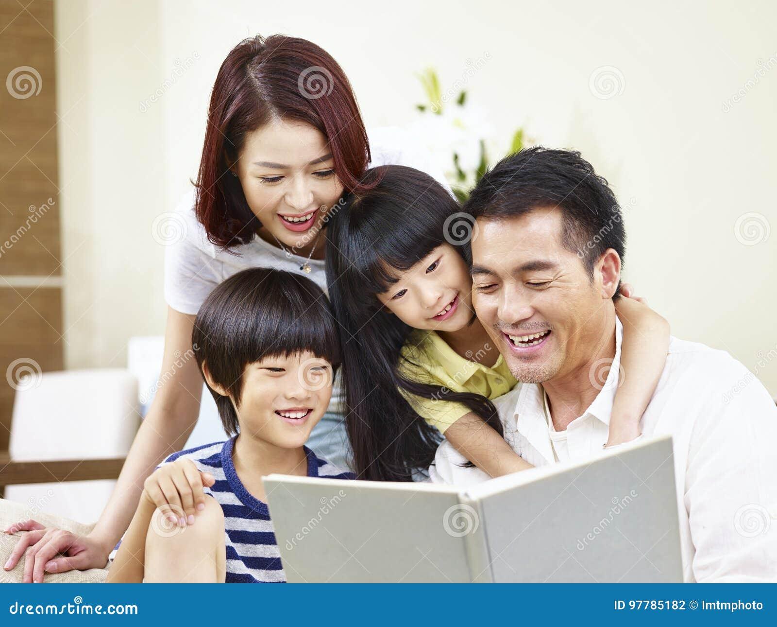Lycklig asiatisk familj som hemma läser en bok