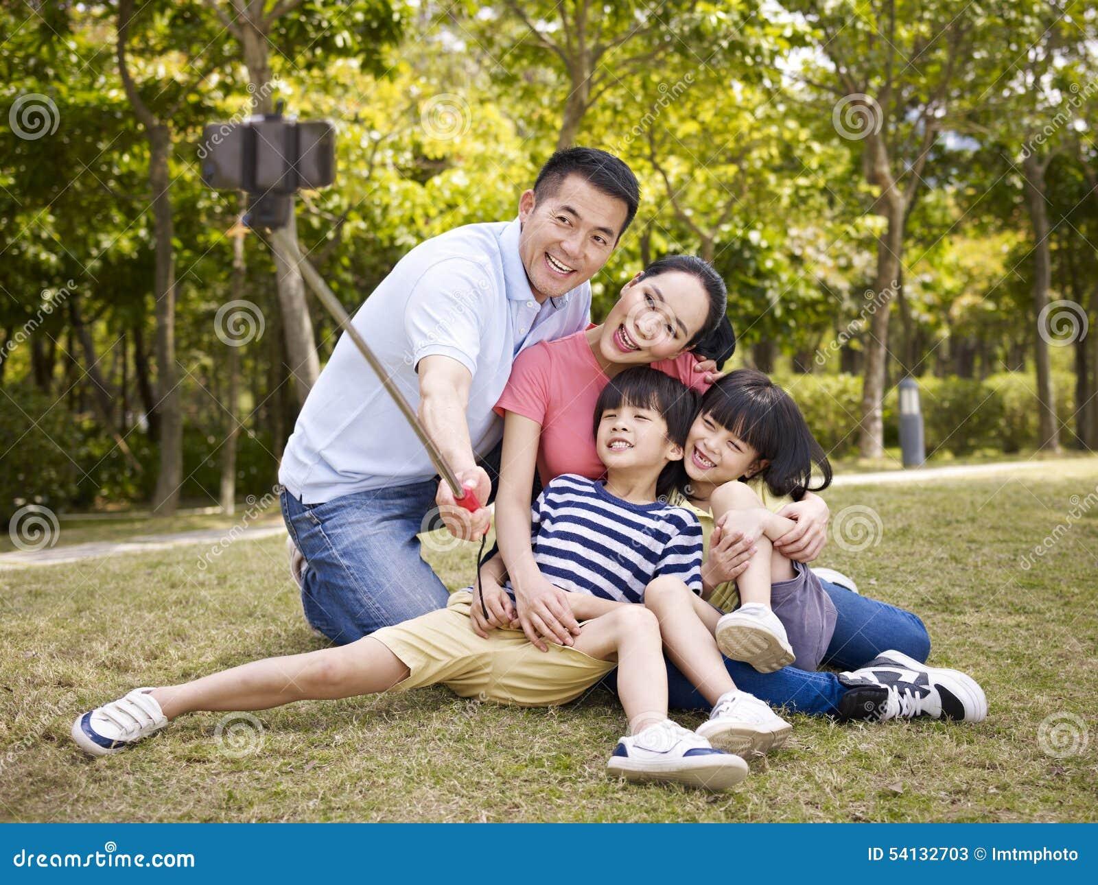 Lycklig asiatisk familj som tar en selfie
