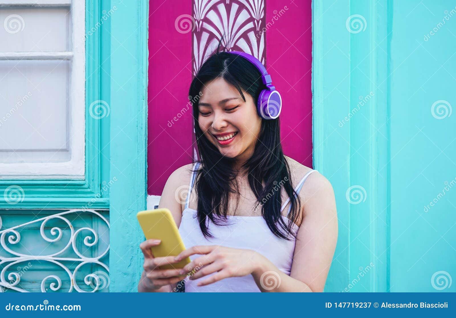 Lycklig asiatisk flicka som lyssnar till musik med utomhus- hörlurar - ung kinesisk kvinna som spelar hennes favorit- playlistmus