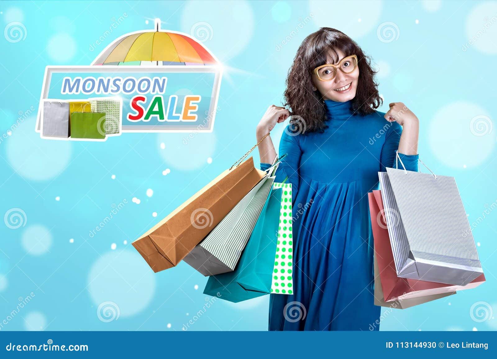 Lycklig asiatisk kvinna med många shoppingpåse på monsunförsäljning