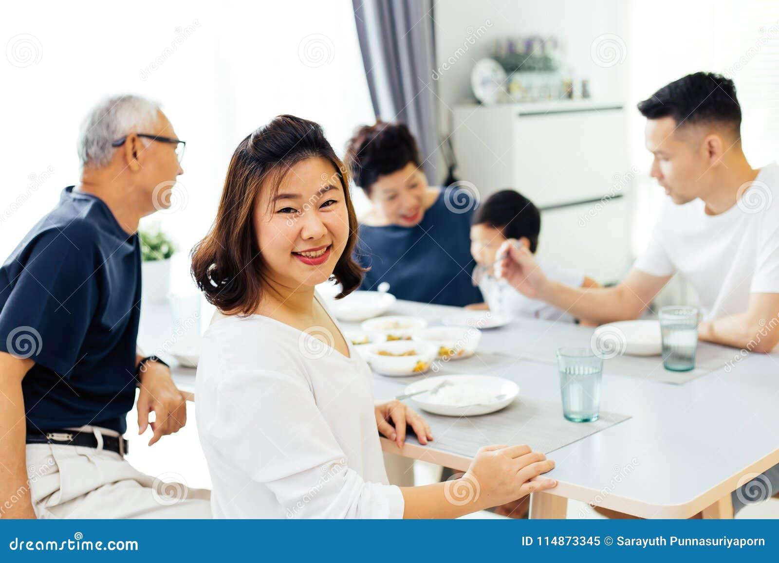 Lycklig asiatisk storfamilj som har matställen hemma mycket av lycka och leenden