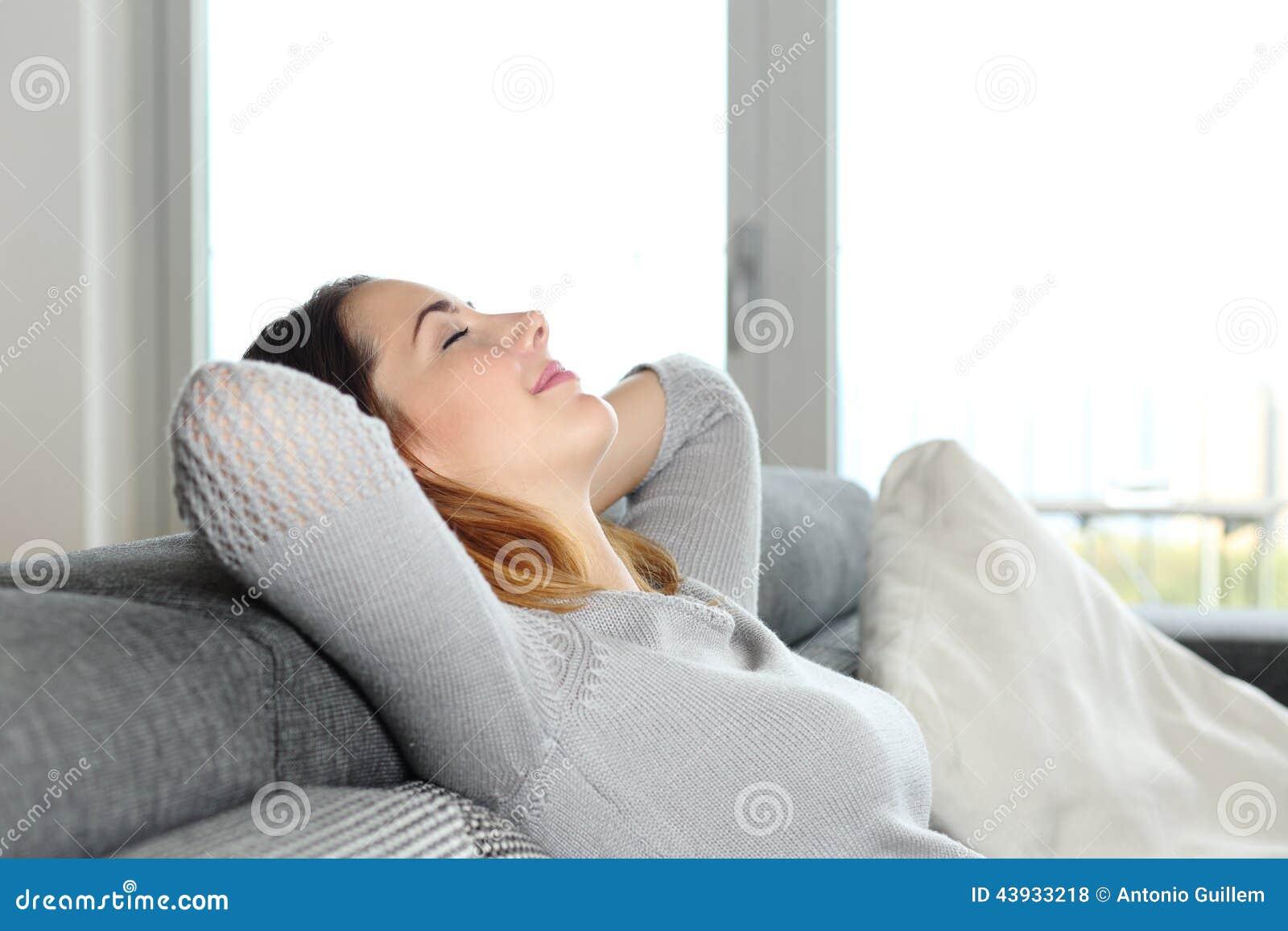 Lycklig avkopplad kvinna som hemma vilar på en soffa