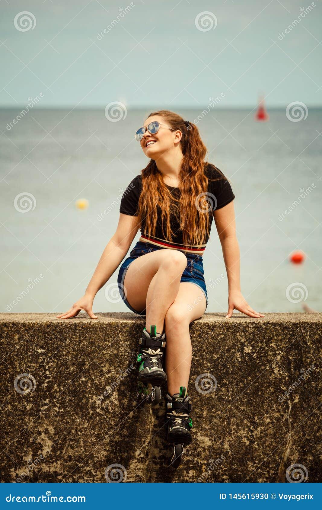 Lycklig b?rande rullskridskor f?r ung kvinna