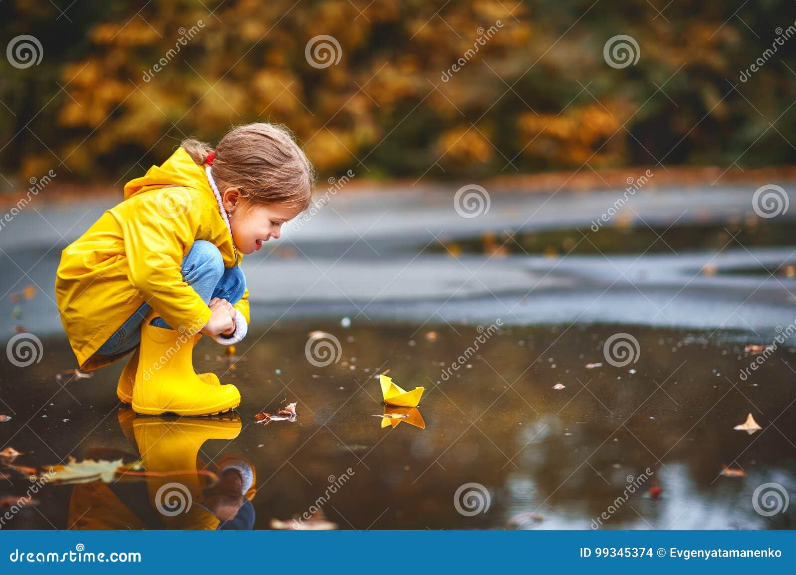Lycklig barnflicka med det pappers- fartyget i pöl i höst på natu