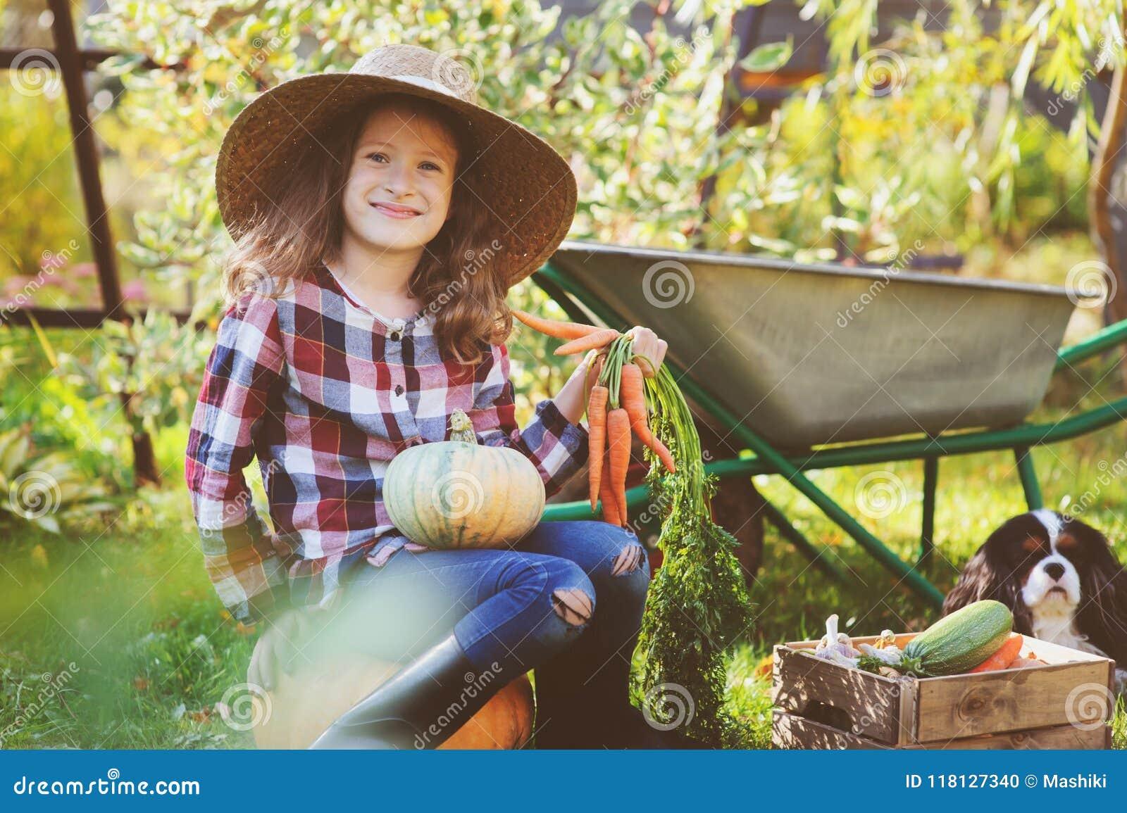 Lycklig barnflicka med spanielhunden som spelar den lilla bonden i höstträdgård