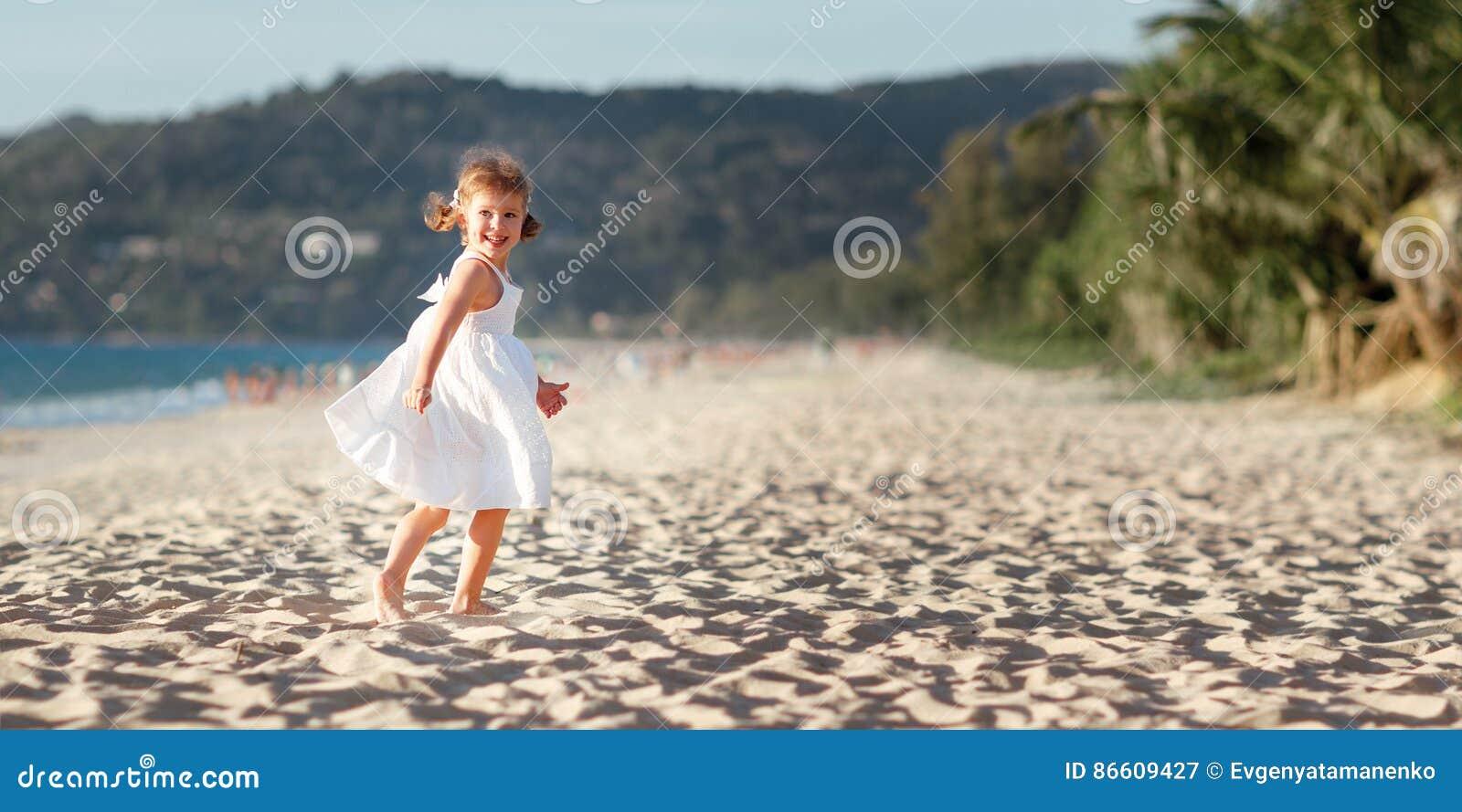 Lycklig barnflickaspring på stranden vid havet i sommar