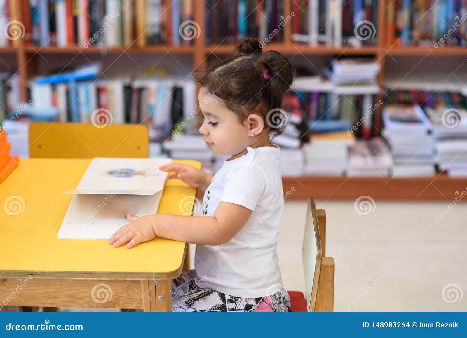 Lycklig barnliten flicka som l?ser en bok