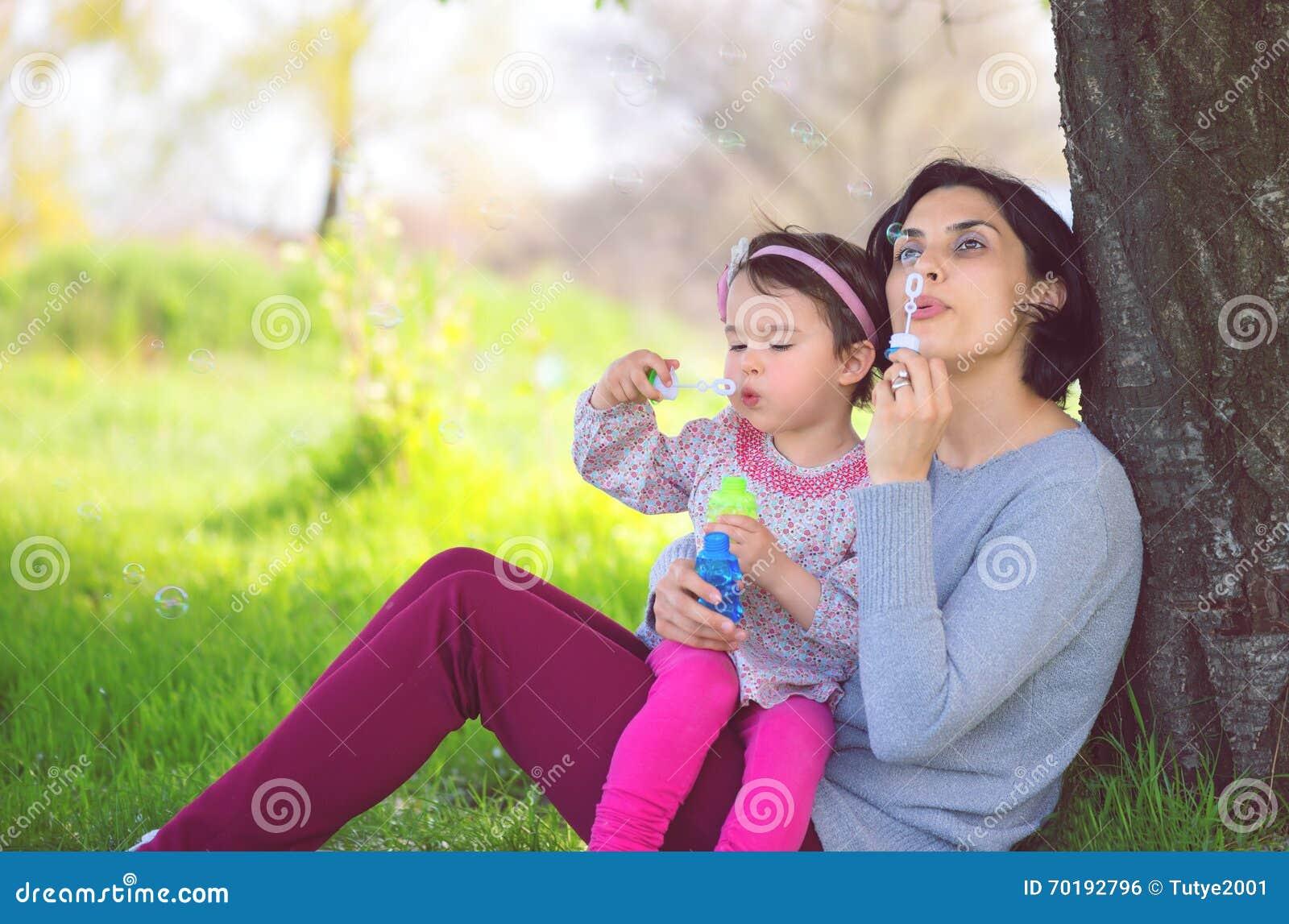 Lycklig barnmoder och hennes dotter som blåser såpbubblor