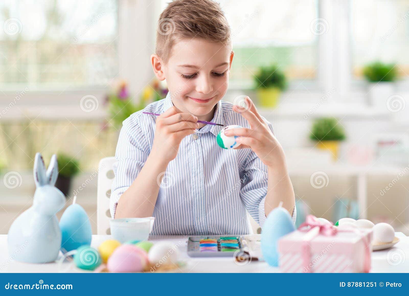 Lycklig barnpojke som har gyckel under målningägg för påsk i vår