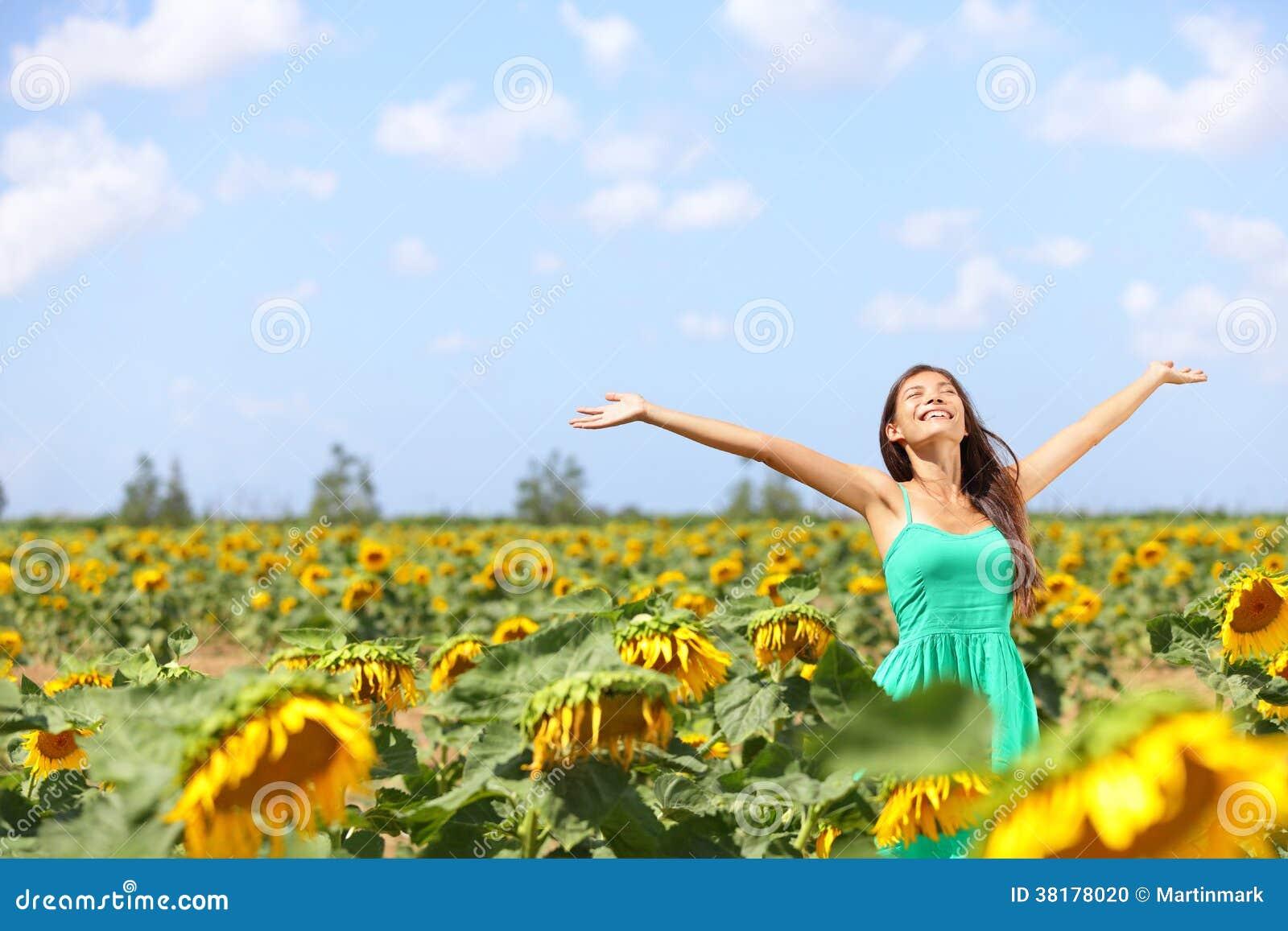 Lycklig bekymmerslös sommarflicka i solrosfält