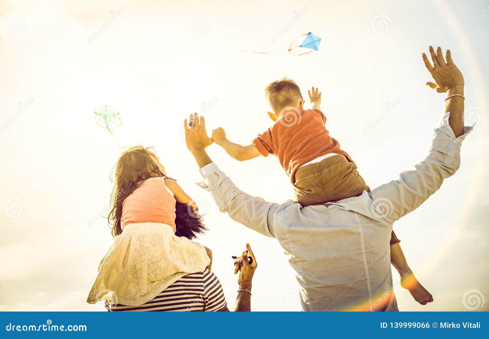 Lycklig blandras- familjgrupp med föräldrar och barn som spelar med draken på strandsemestern - sommarglädjebegrepp