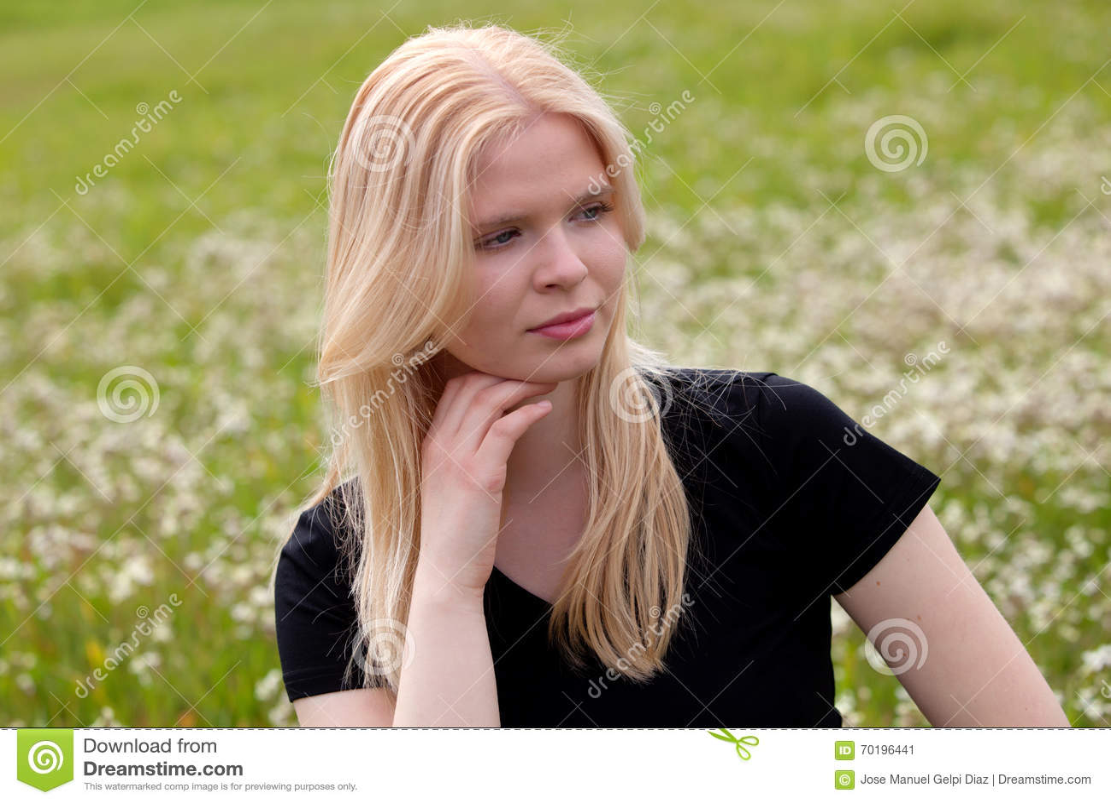 Lycklig blond flicka som omges av blommor