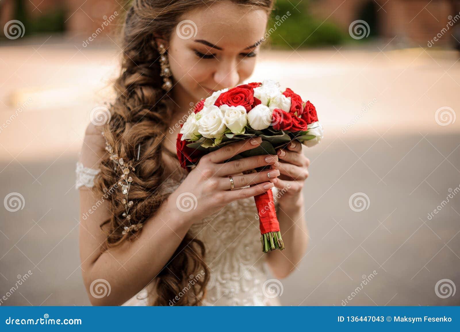 Lycklig brud i en bröllopsklänning med en flätad trådfrisyr som sniffar en bukett av rosor