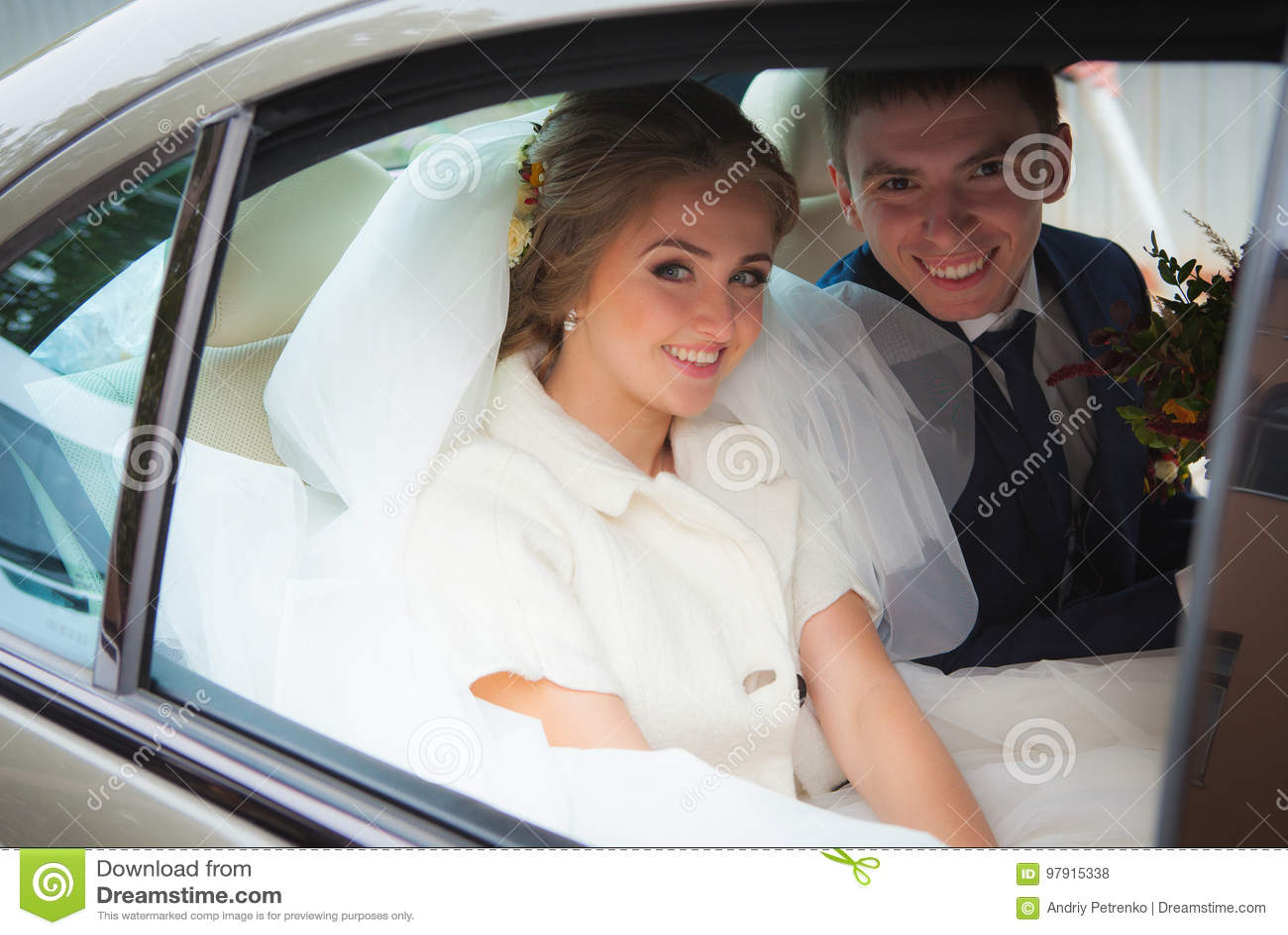 Lycklig brud och brudgum i bilen