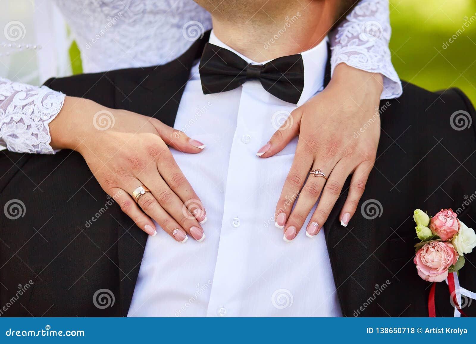 Lycklig brud som kramar brudgummen med händer Närbildstående av en brud och en brudgum