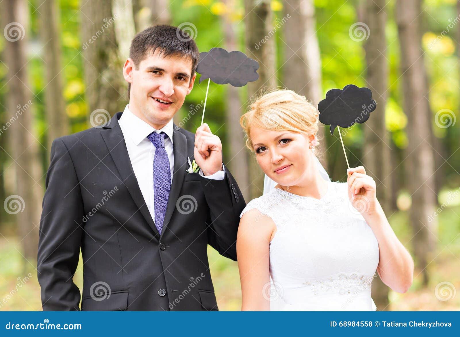 Lycklig brudgum och brud i en parkera med tecken