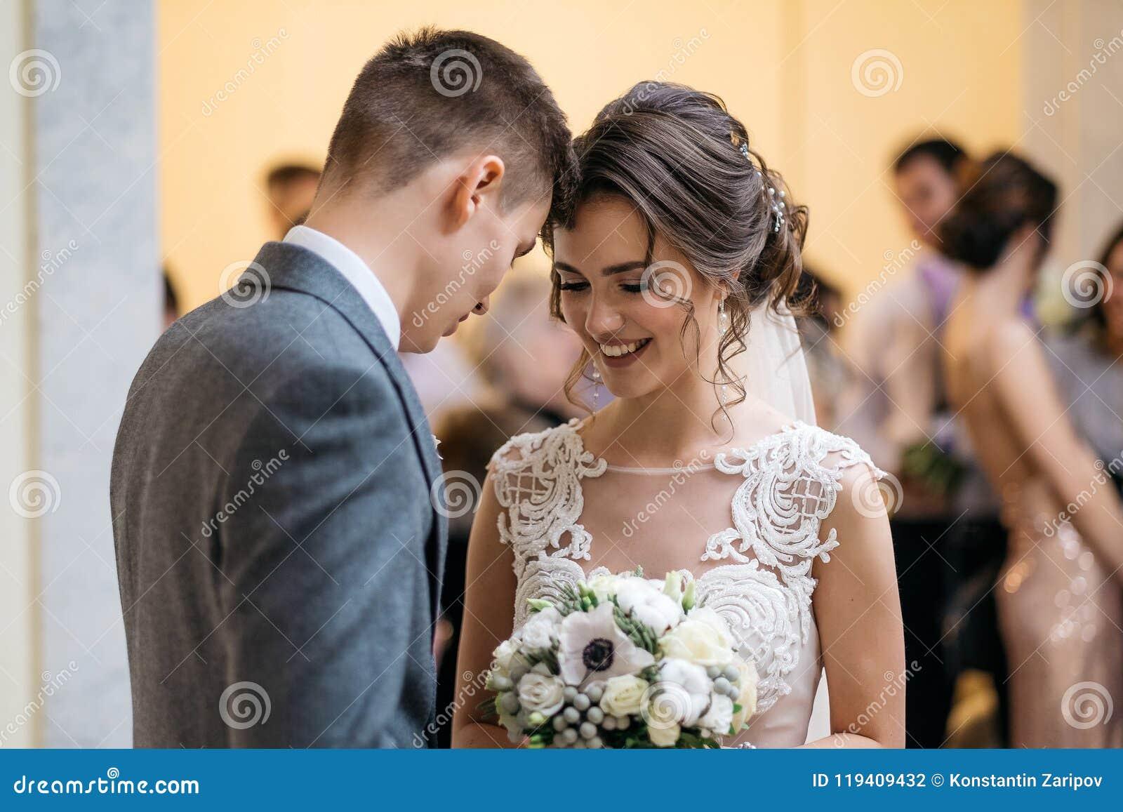 Lycklig brudgum och brud i registreringskontoret Bröllopgäster i en suddig bakgrund