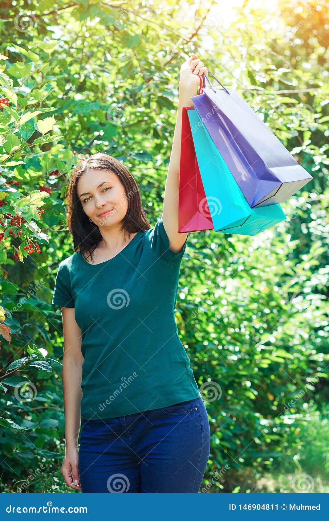 Lycklig brunettkvinna efter stora shoppa försäljningar som upp rymmer färgrika shoppa påsar