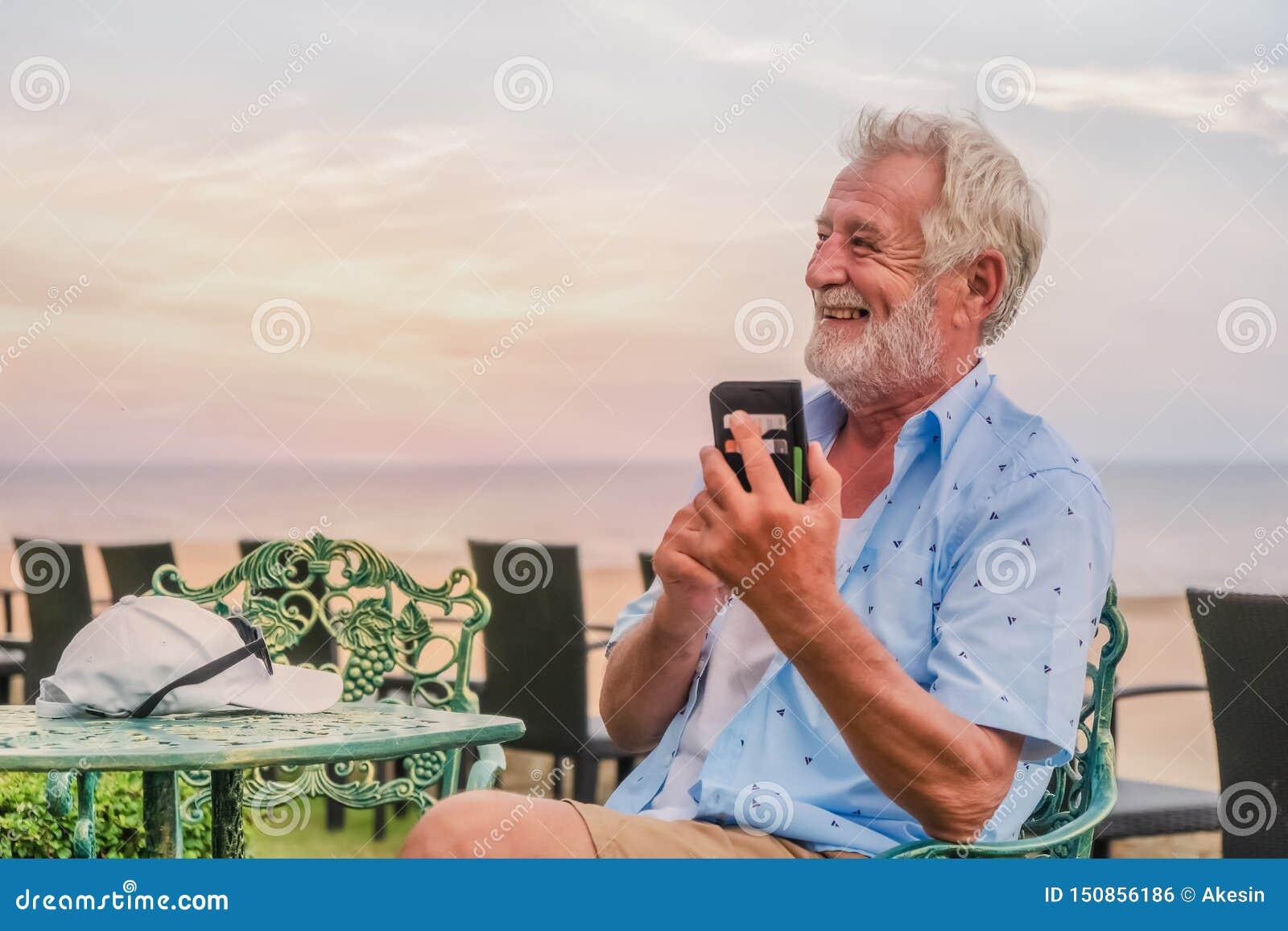 Lycklig caucasian man som använder smartphonen för pratstund och selfie
