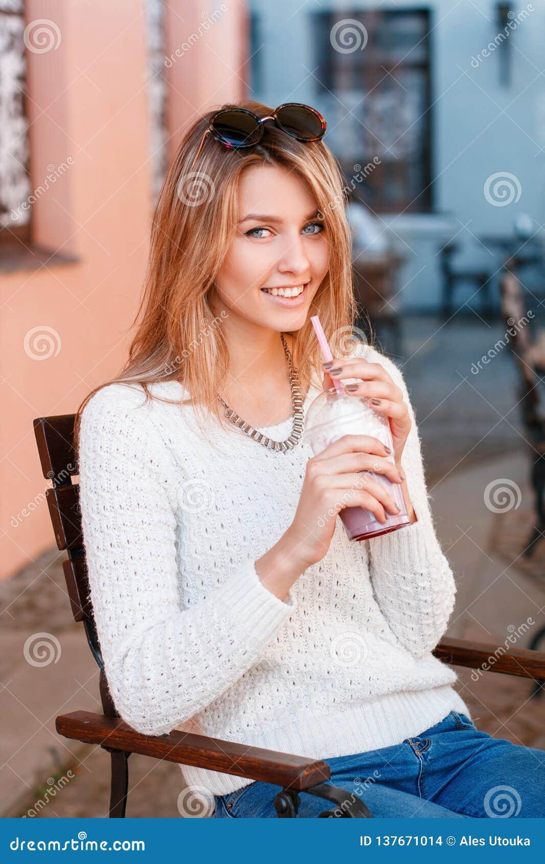 Lycklig charmig ung hipsterkvinna med ett härligt leende i en stucken tröja i jeans med solglasögon