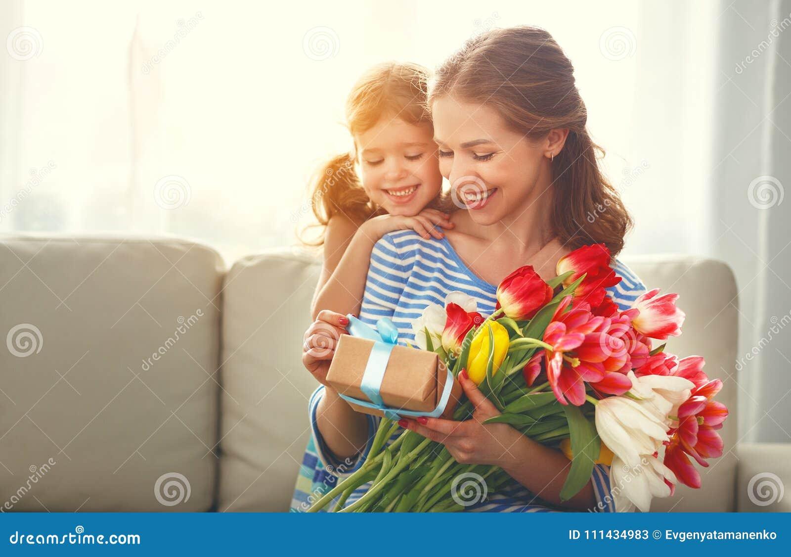 Lycklig dag för moder` s! barndottern ger modern en bukett av f