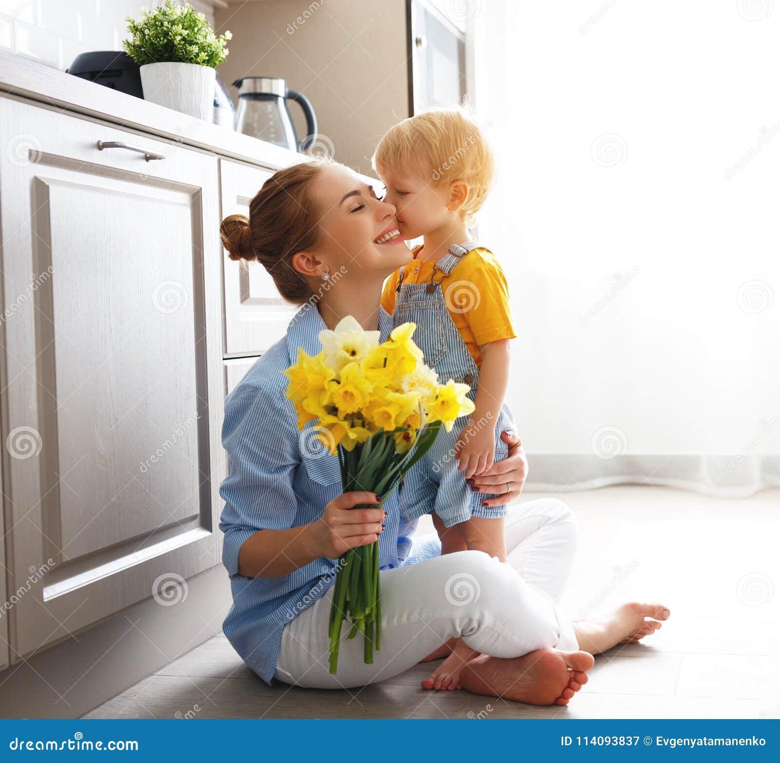 Lycklig dag för moder` s! behandla som ett barn sonen ger flowersformodern på ferie