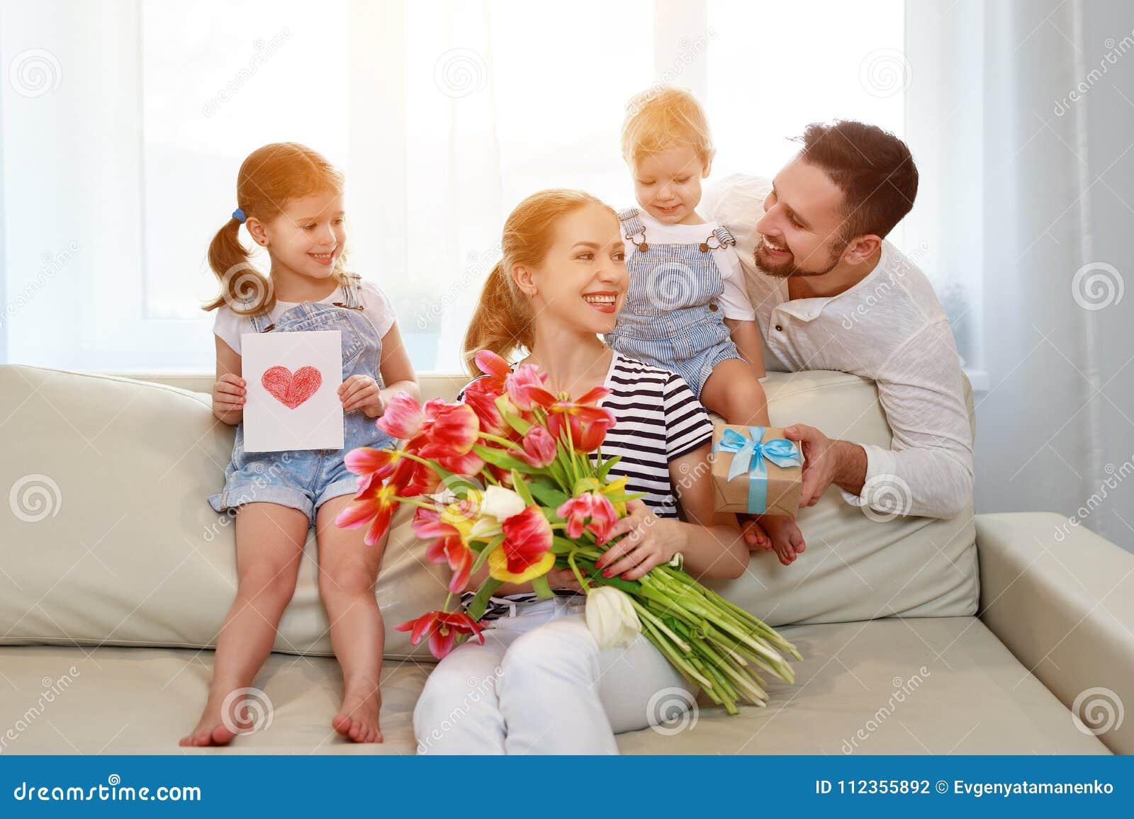 Lycklig dag för moder` s! fadern och barn gratulerar modern på H