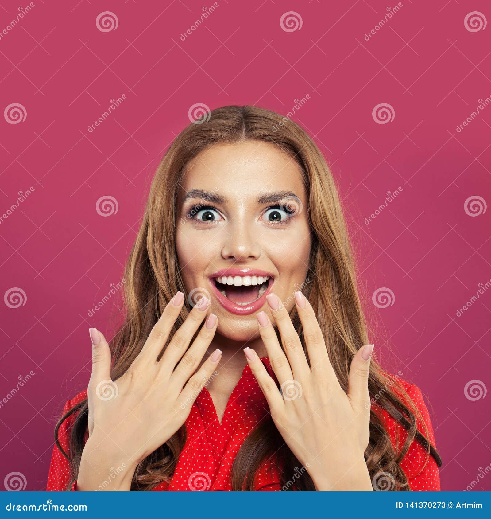Lycklig förvånad flickastående Härlig ung upphetsad kvinna på färgrik ljus rosa bakgrund