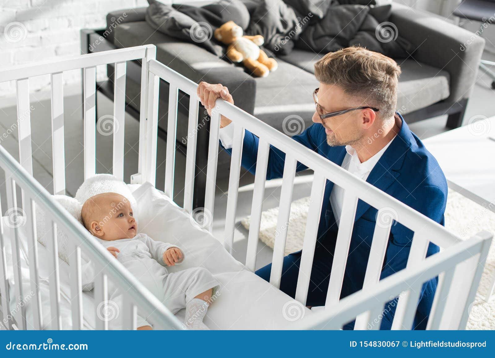 Lycklig fader i formella kläder som sitter nära begynnande dotter