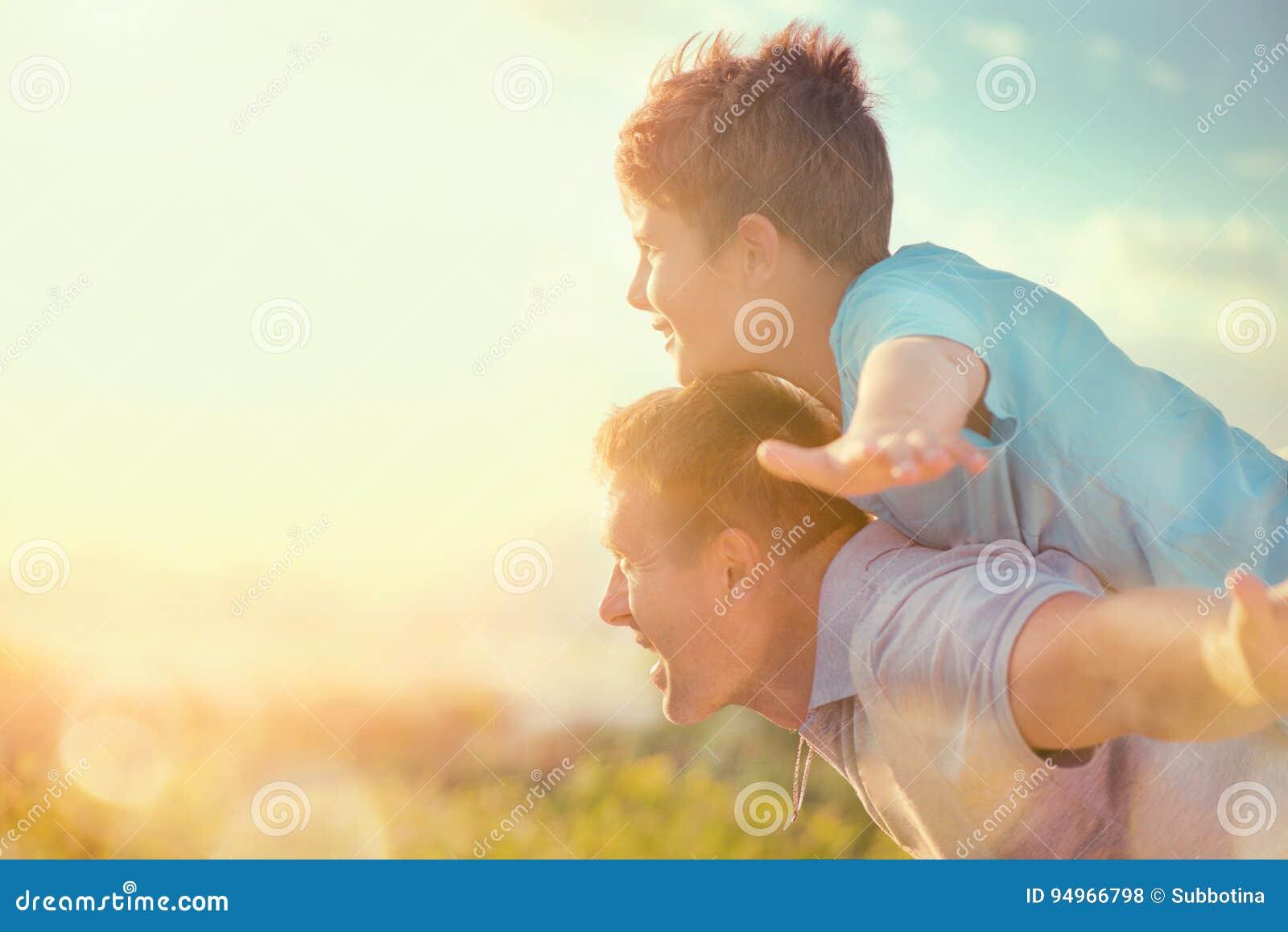 Lycklig fader och son som har gyckel över härlig himmel utomhus
